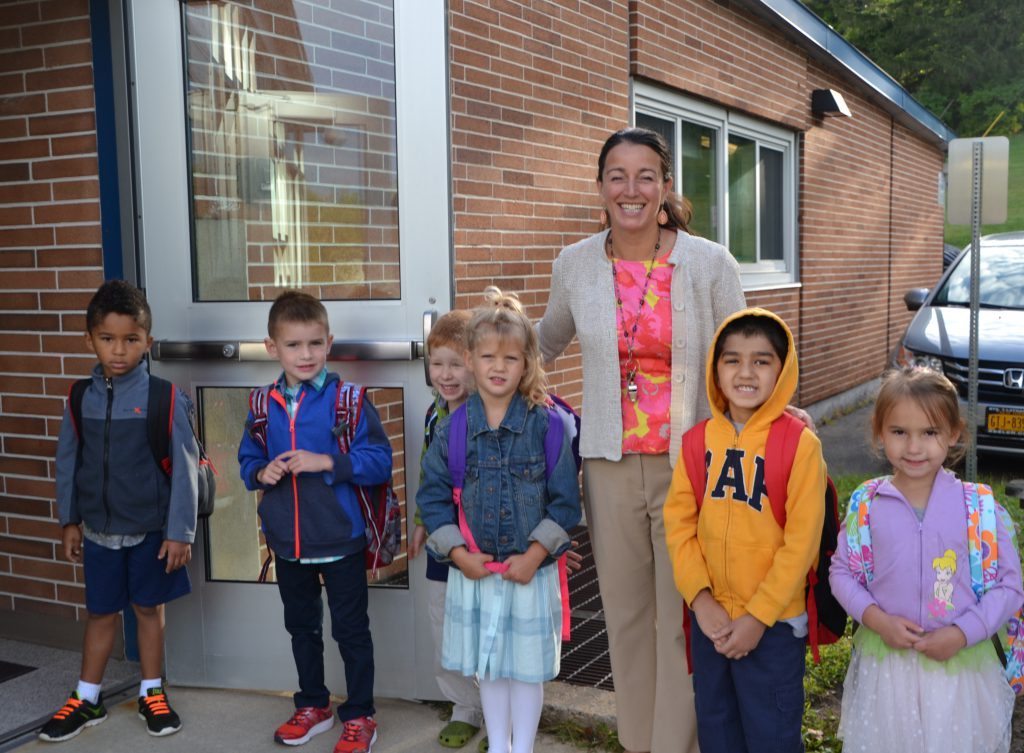 Hillside Principal Dr. Shireen Fasciglione stands by the front door with six kindergarten students.