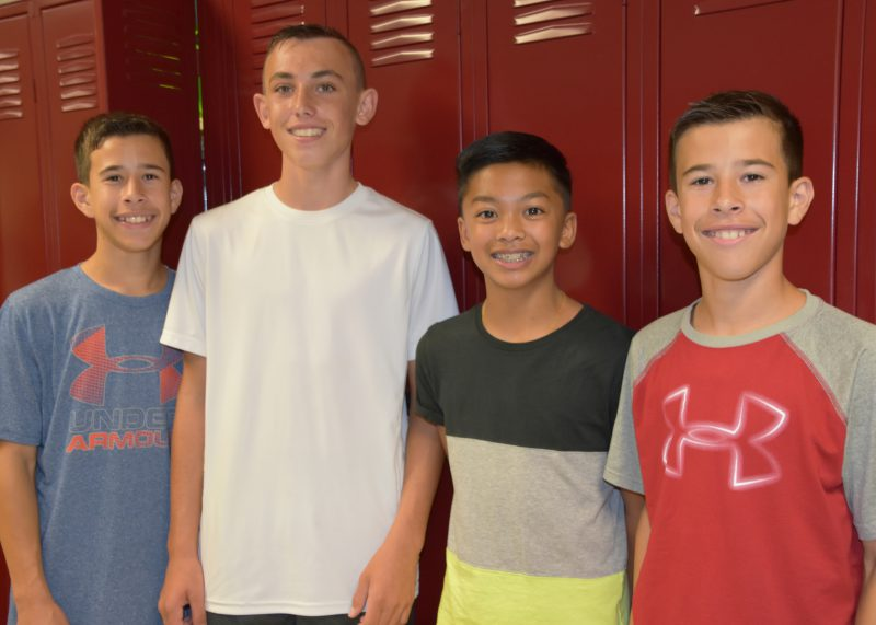 Group of four boys in front of their lockers smiling at the camera