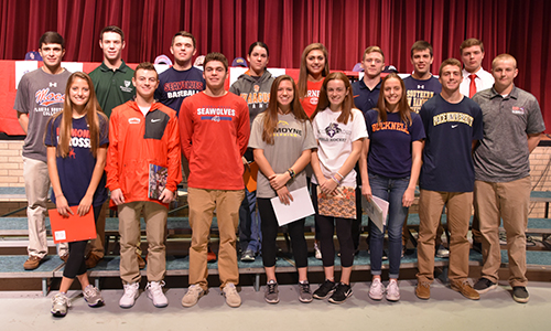 Sixteen student-athletes, wearing college apparel, stand in front of the Niskayuna High School stage.