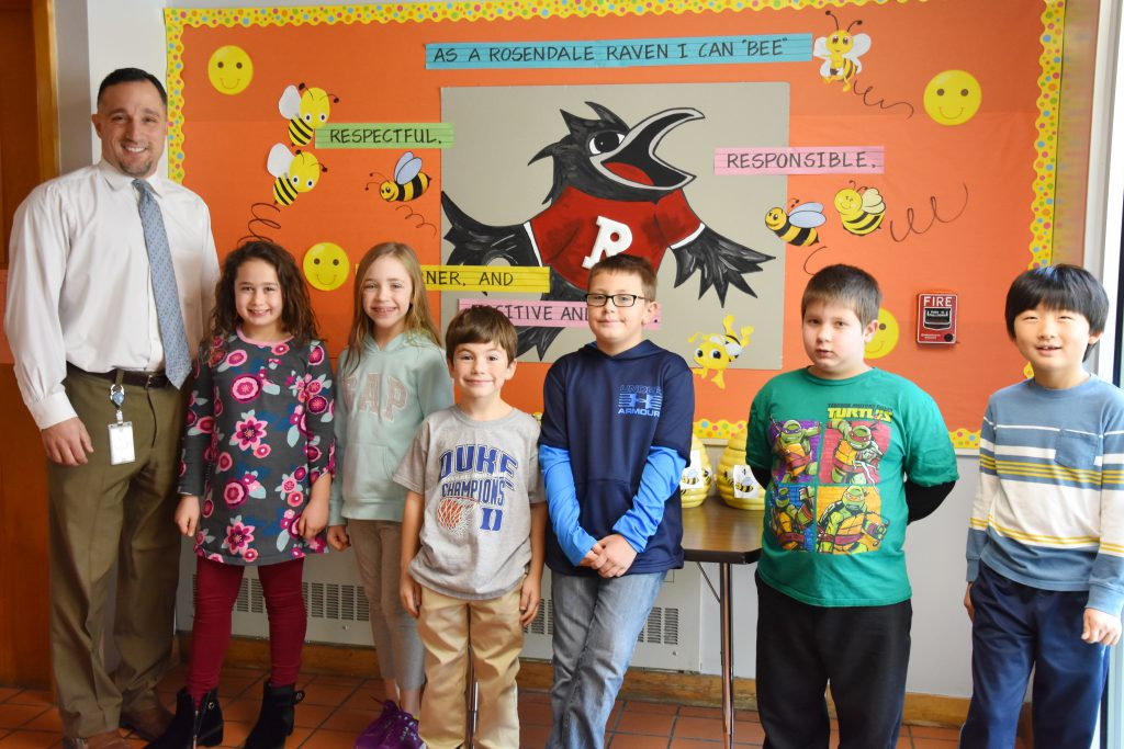 Rosendale Principal Joseph DiCaprio and six students stand in front of a bulletin board about Rosendale character traits