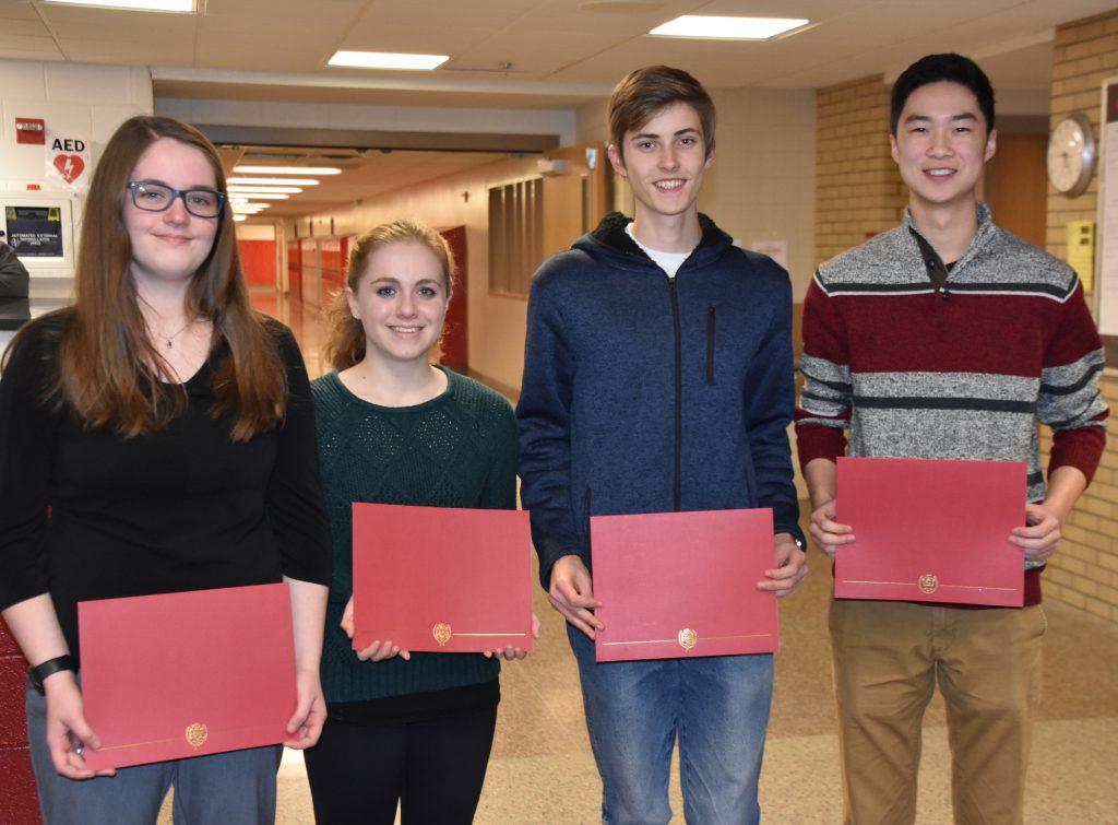 The four 2018 National Merit Scholar contest honorees stand in the hallway at Niskayuna High School holding certificates. The honorees are: Skylar Litz, Johanne I. Friedman, Bryan Zhou and National Hispanic Scholar Gabriel A. Kammer.