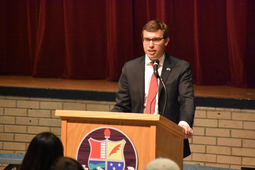 Seth Wyngowski stands at the podium in the front of the Niskayuna High School auditorium and talks to students.