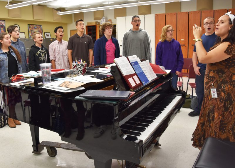 A group of students gathered around a piano singing and watching their teacher conduct them