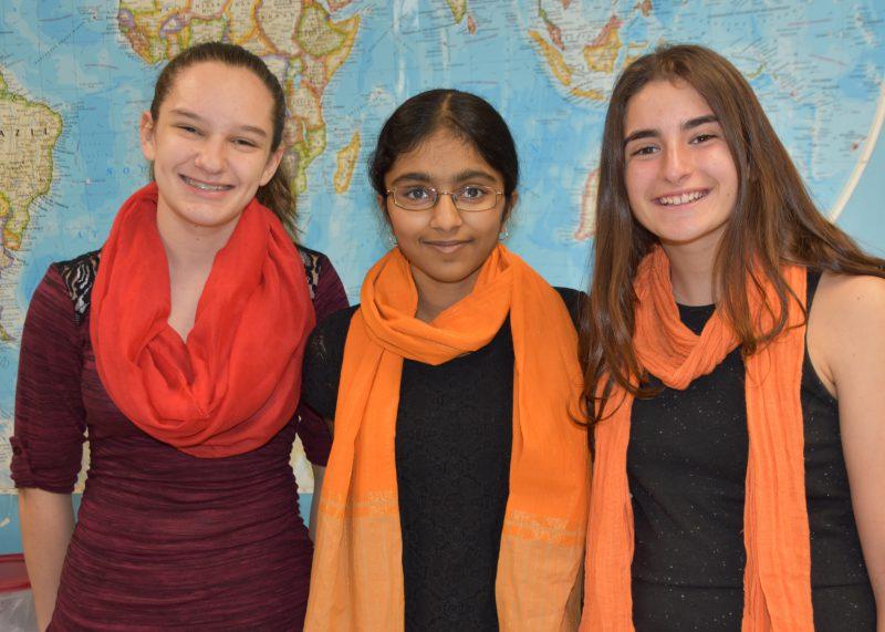 Three girls smiling at the camera wearing orange scarves around their necks