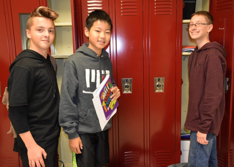 Three boys standing at their lockers, smiling at the camera