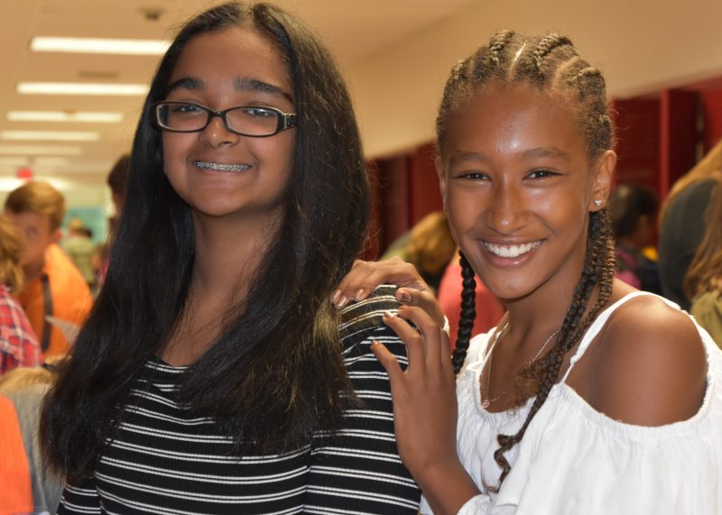 Two girls standing at their locker and smiling