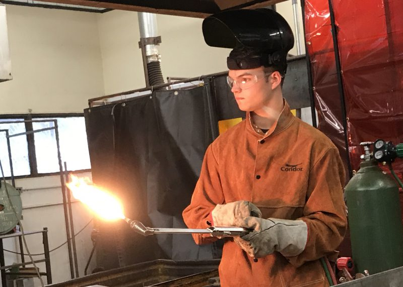 Student using a blow torch during welding class