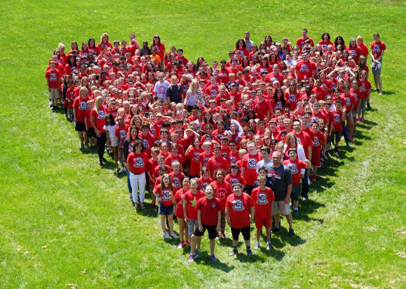 Dozens of students standing in a heart formation wearing red shirts