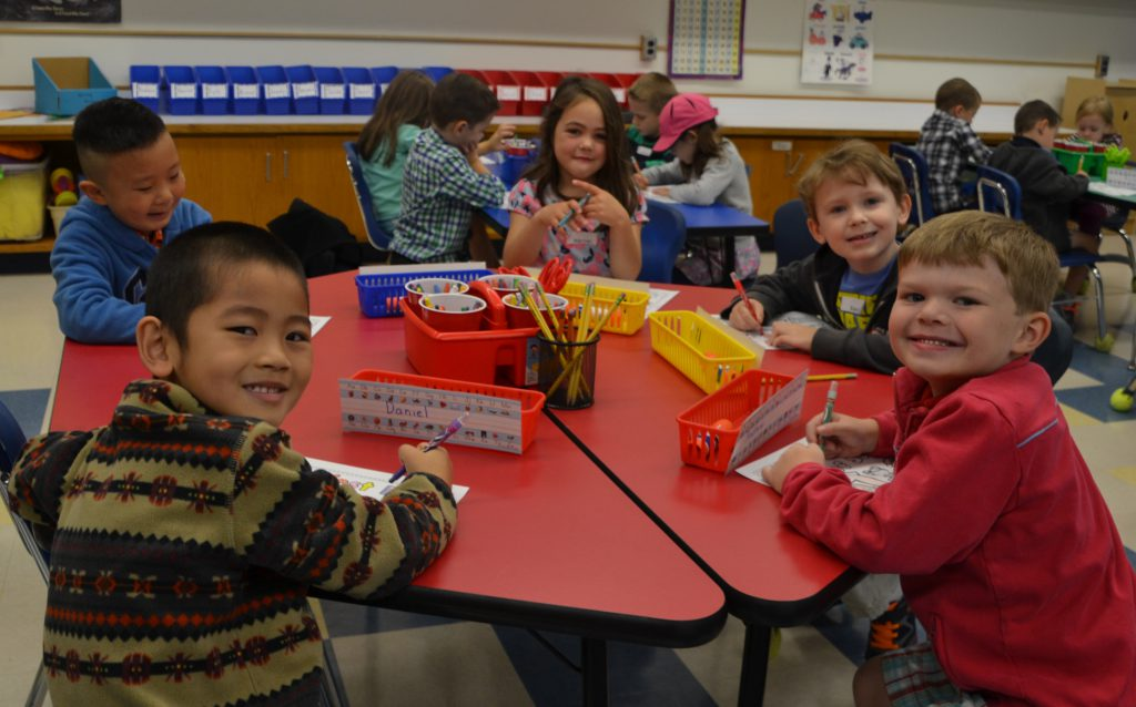 Five Birchwood kindergarten students sit at their table and smile.