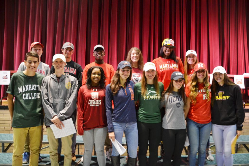 Fourteen Niskayuna High School student-athletes stand in front of the stage in the Niskayuna High School auditorium wearing hats and shirts of the colleges they will attend.