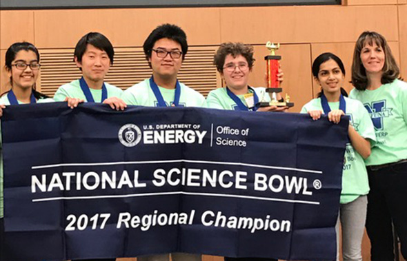 The five members of the Van Antwerp Science Bowl team and coach Karen Postlethwait stand with their championship banner at the Global Research Center.