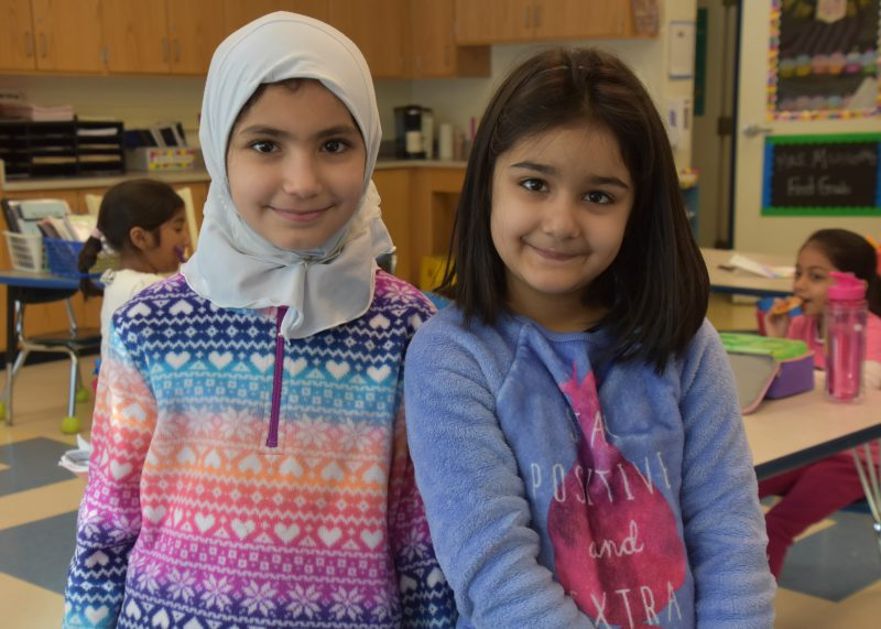Two students standing together smiling at the camera