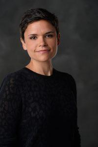 Headshot of Kate Fagan in a black shirt smiling at the camera
