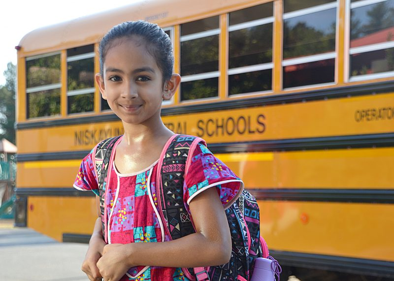 Student standing in front of a school bus smiling