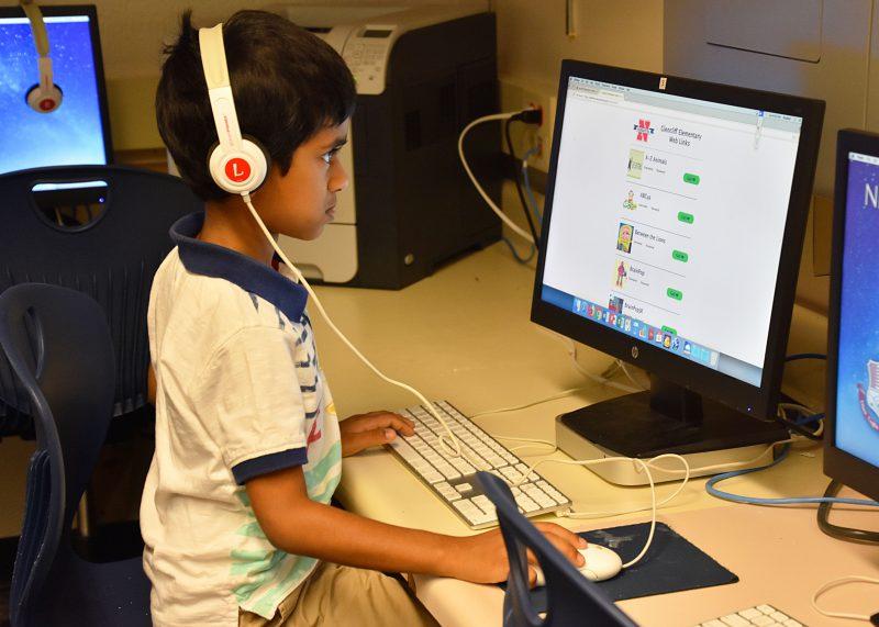 Student wearing headphones facing the computer