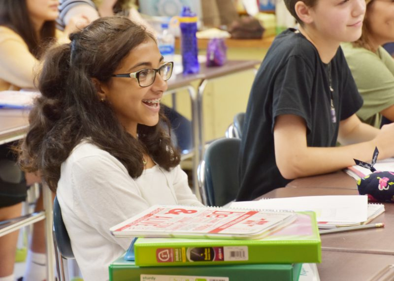 A student is sitting at a table and smiling with a stack of books and binders nearby.