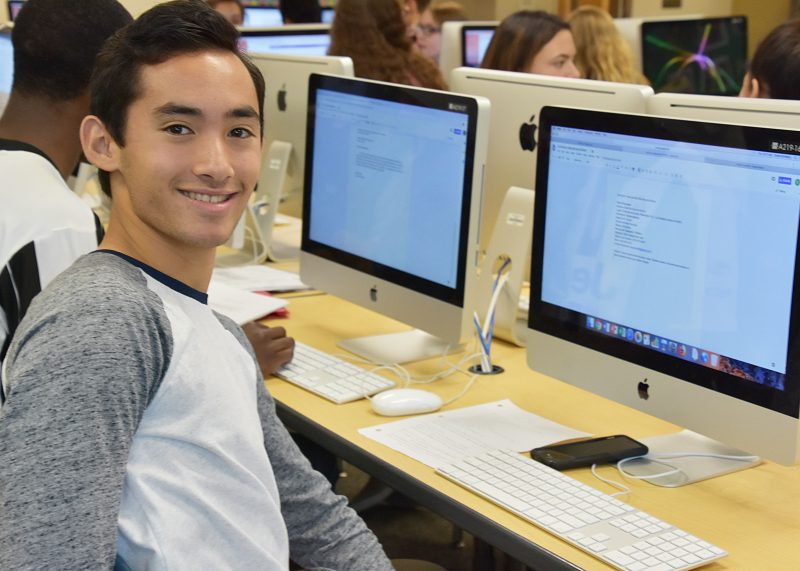 Student sitting in front of a computer turned smiling at the camera