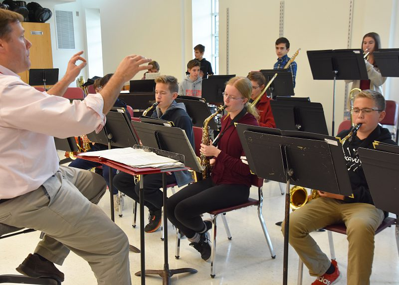 Teacher conducting students playing a variety of instruments