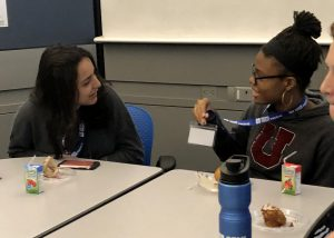 two students talking at a lunch table