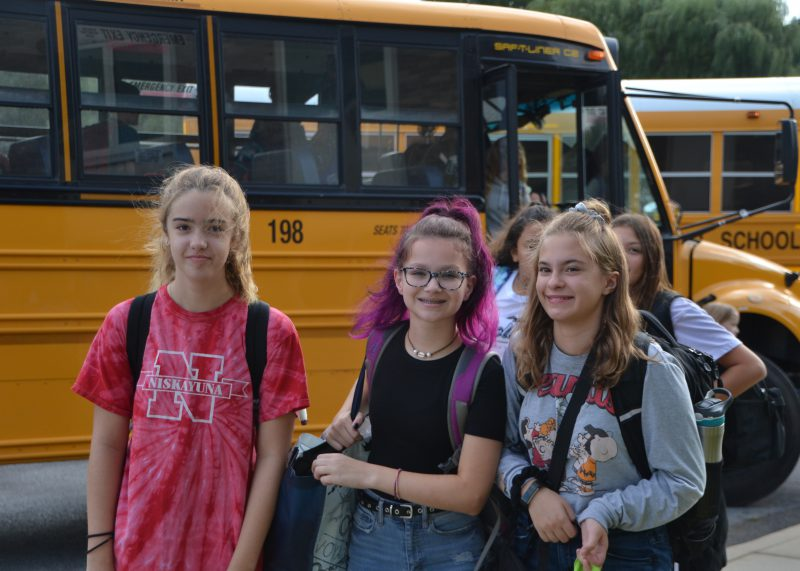 middle school girls by a bus