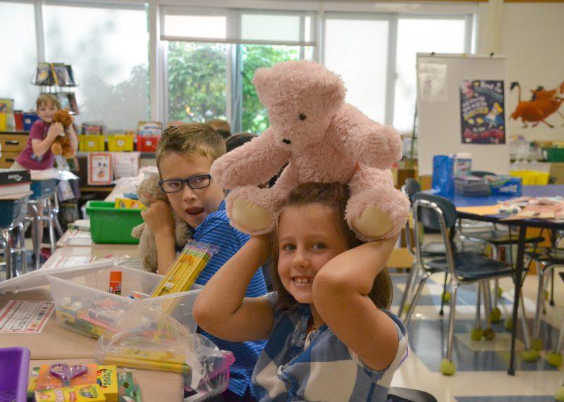 girl holding stuffed bear over her head
