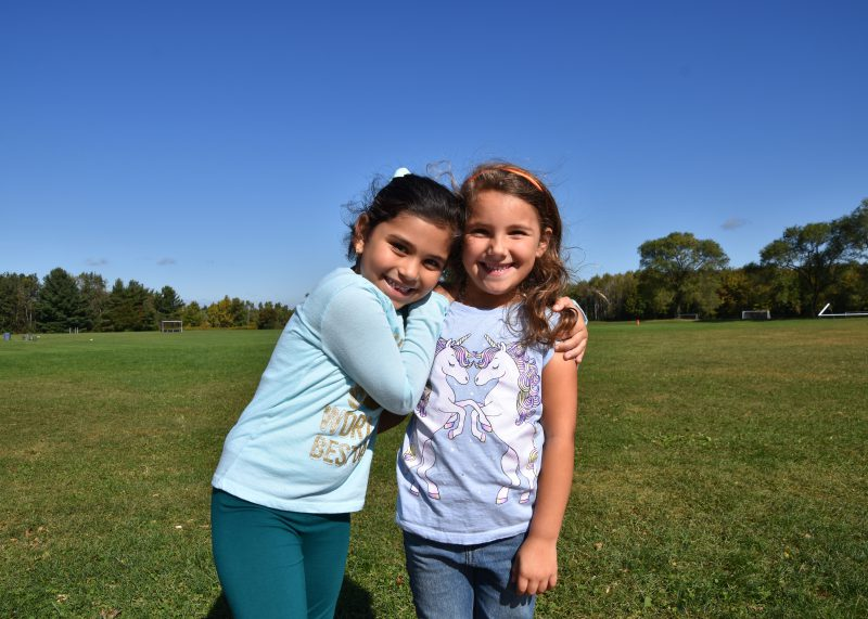 two elementary girls hugging