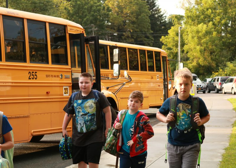 elementary boys carrying book bags