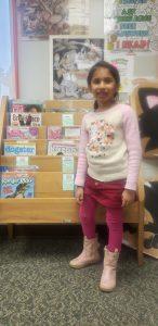 first grade girl standing behind books