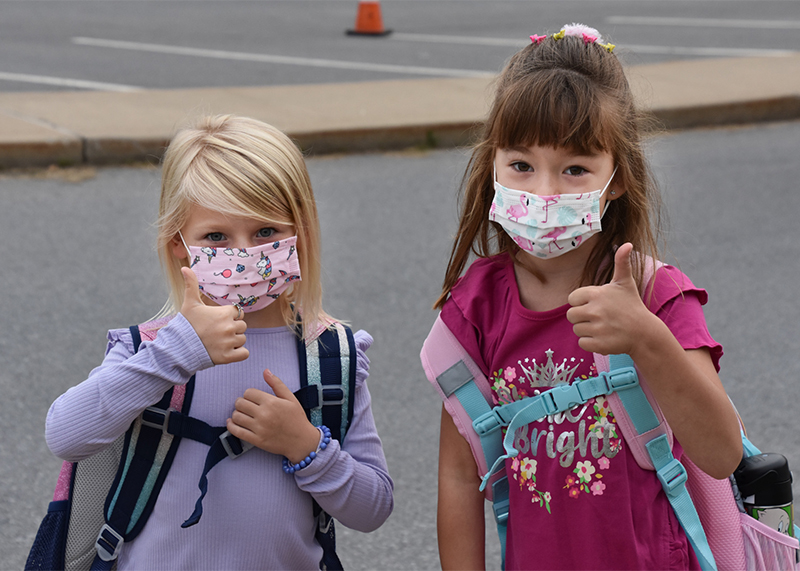 two girls wearing masks giving thumbs up