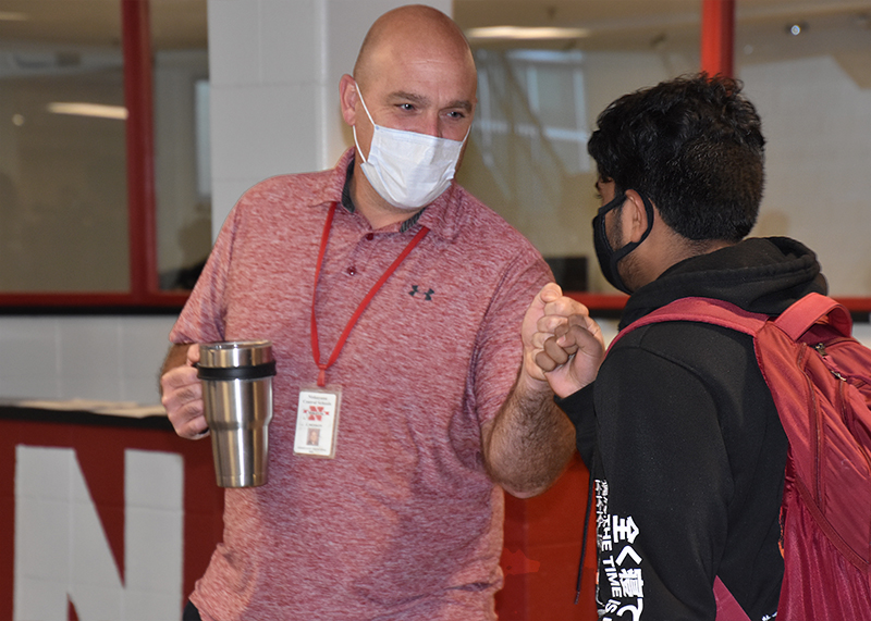 student fist bumps administrator in hallway