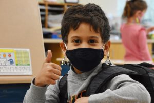 photo of an elementary student giving a thumbs up